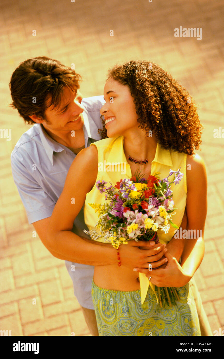 High angle view of a young man embracing a teenage girl from behind - Stock Image