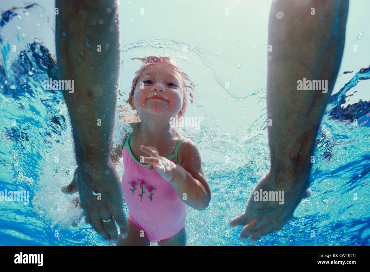 Close-up of father's hands reaching out to his daughter underwater - Stock Image