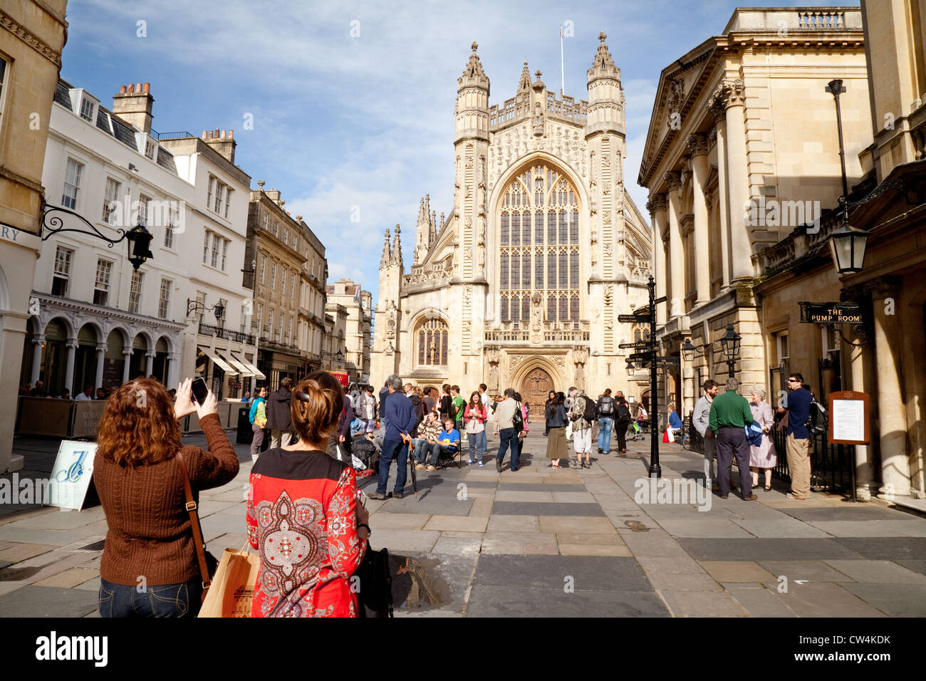 Tourists taking a photo of Bath Abbey on a sunny summers day, the city center, Bath Somerset UK Stock Photo
