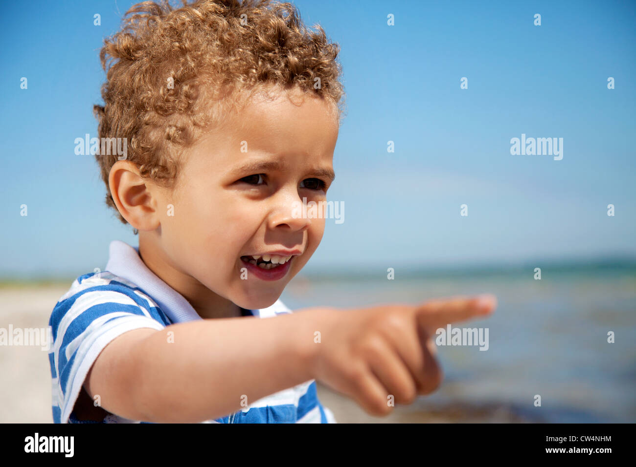 Adorable little kid pointing at something interesting outdoors - Stock Image