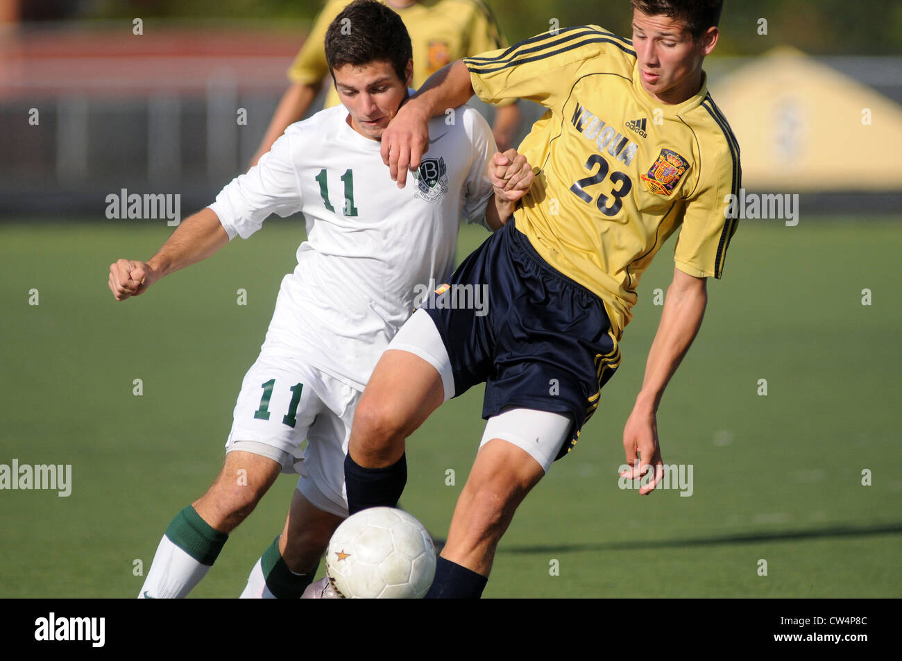 Soccer Players battle along the side line during a high school match. - Stock Image