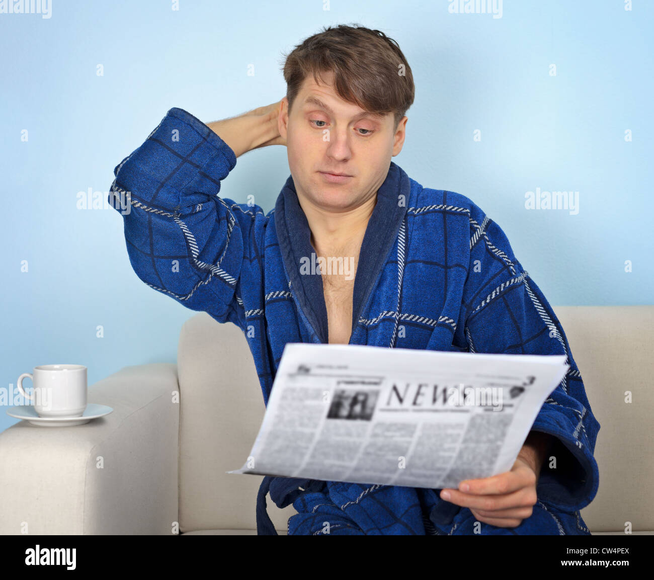 Person reads a newspaper with pensiveness on blue background - Stock Image