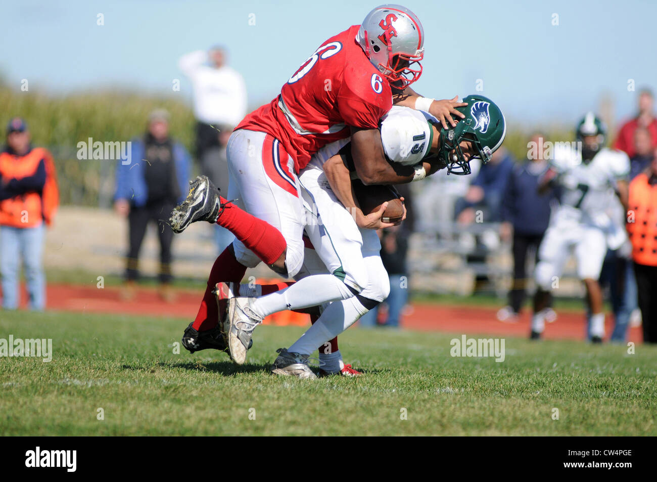 Football Defensive player sacks quarterback during a high school game. - Stock Image