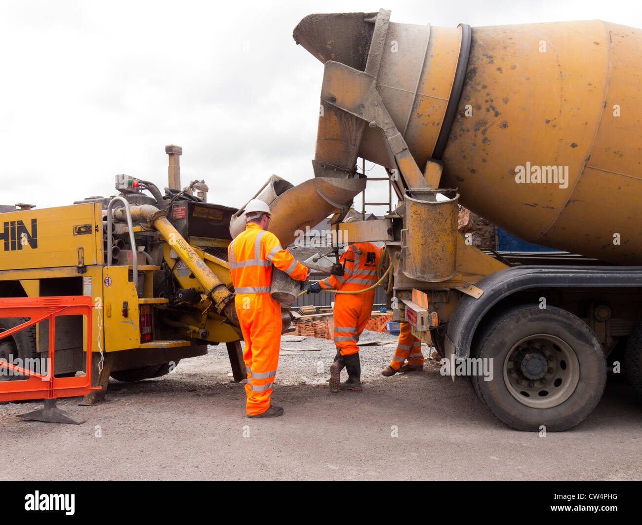 Construction workers and cement truck. - Stock Image
