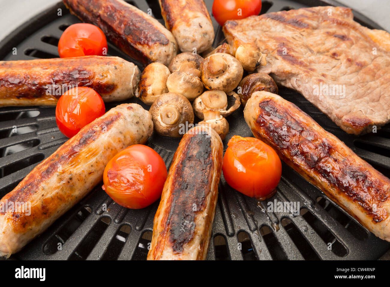 Sausages and steak on the barbecue with some tomato's and mushrooms - Stock Image