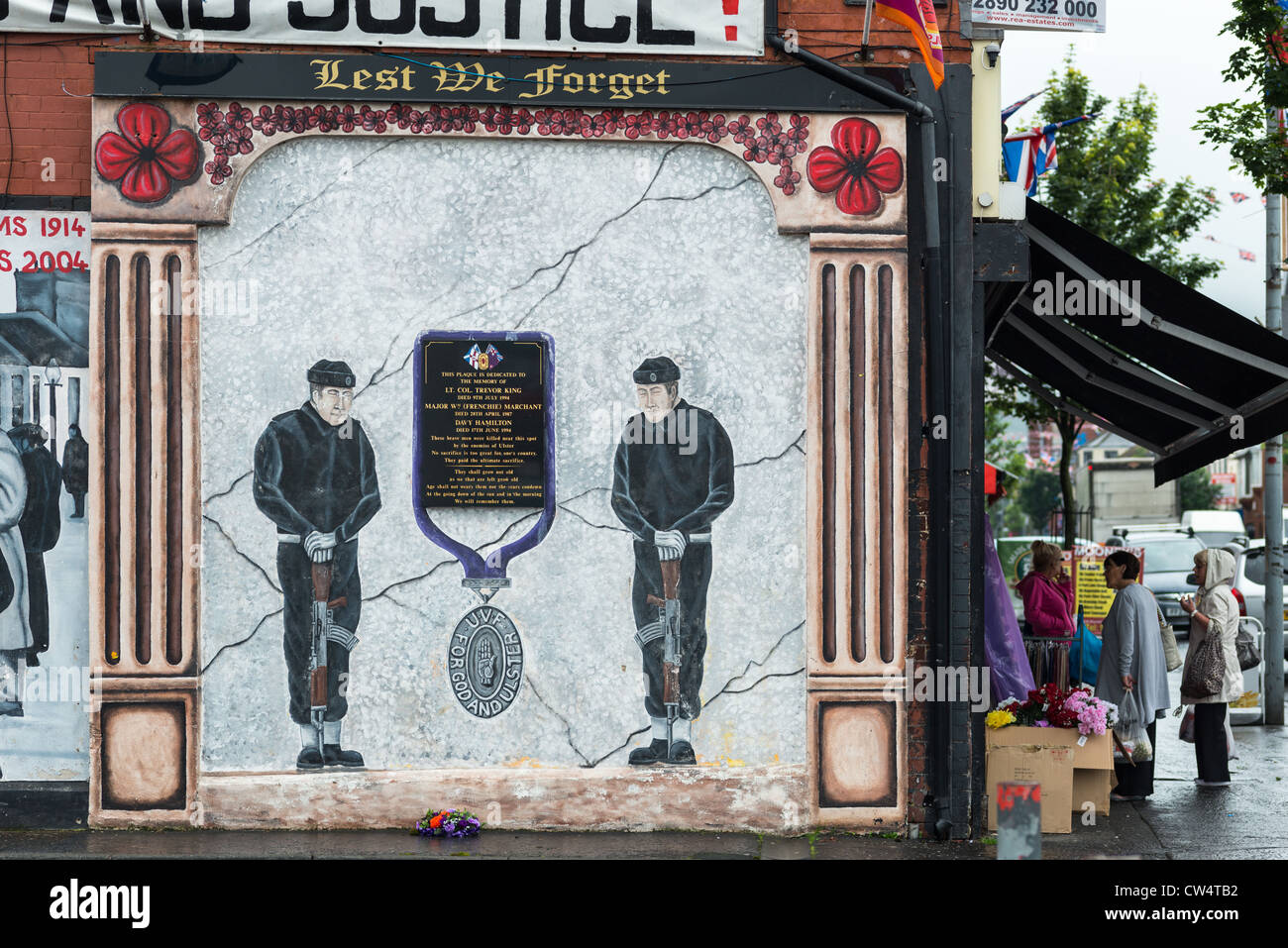 Local people at grocers with Political mural on Shankill road, Belfast in Northern Ireland. - Stock Image