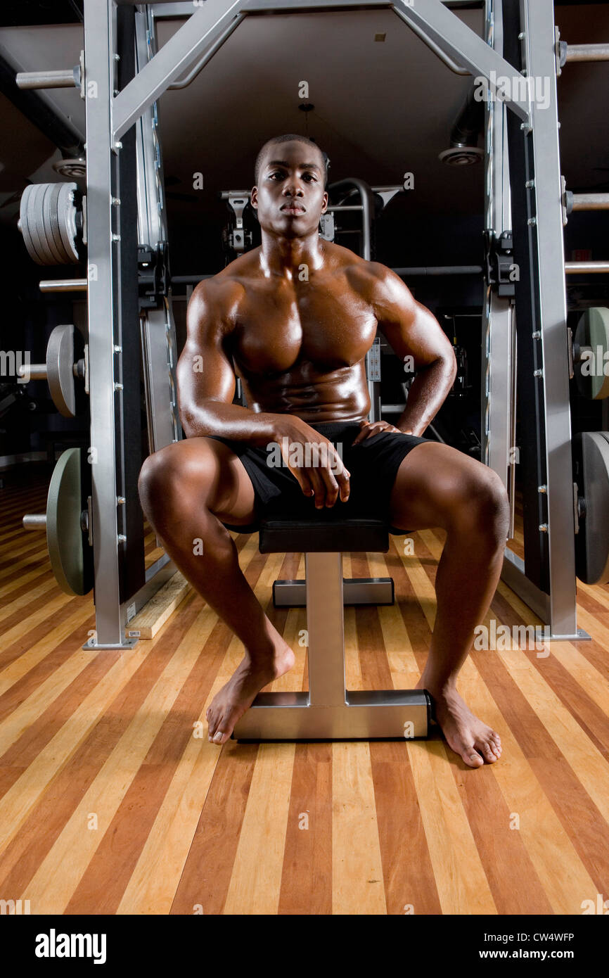 Portrait of a shirtless young man sitting in the gym - Stock Image