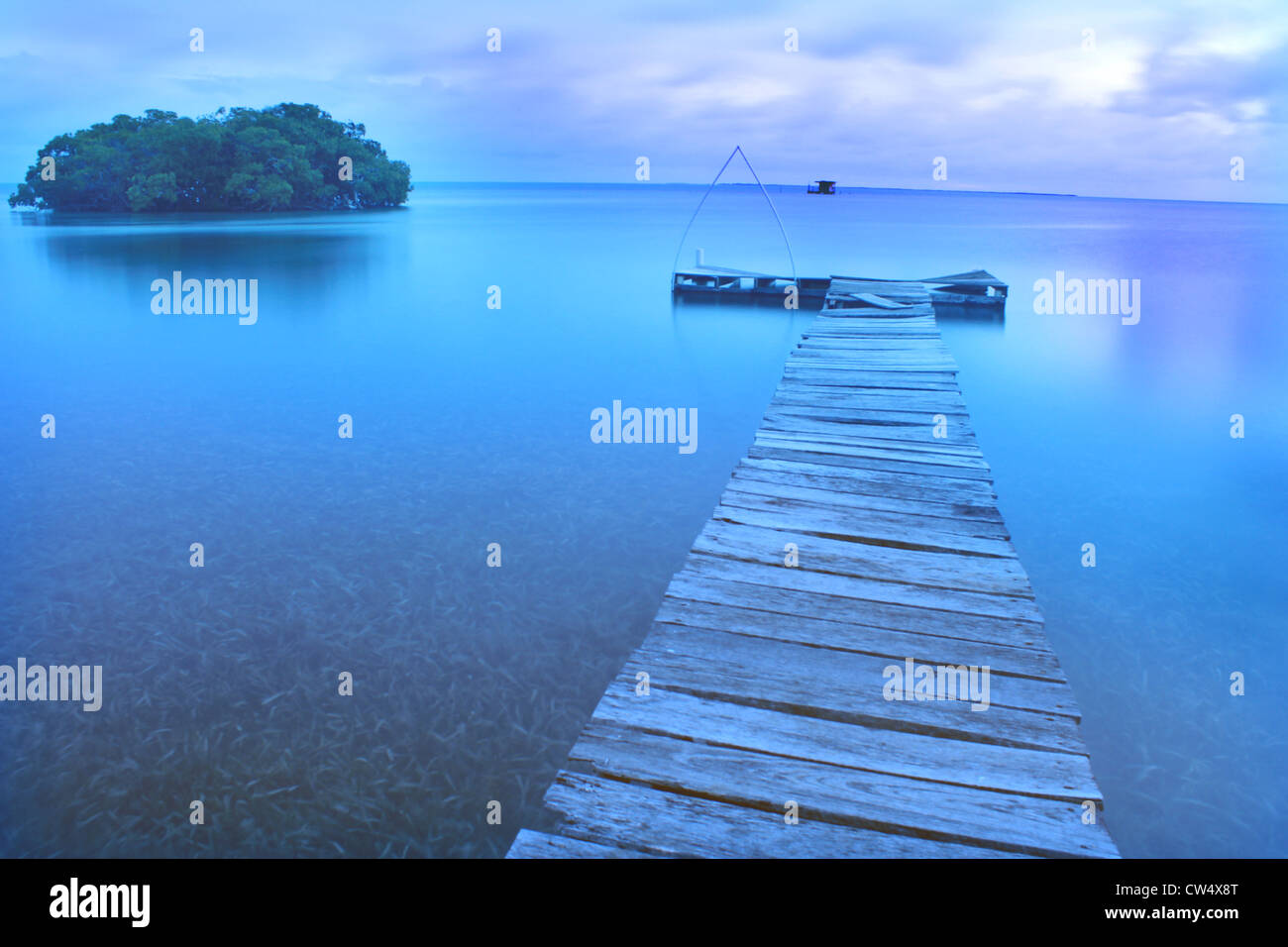 Calm evening with a dock on Caribean with ocean and island - Stock Image