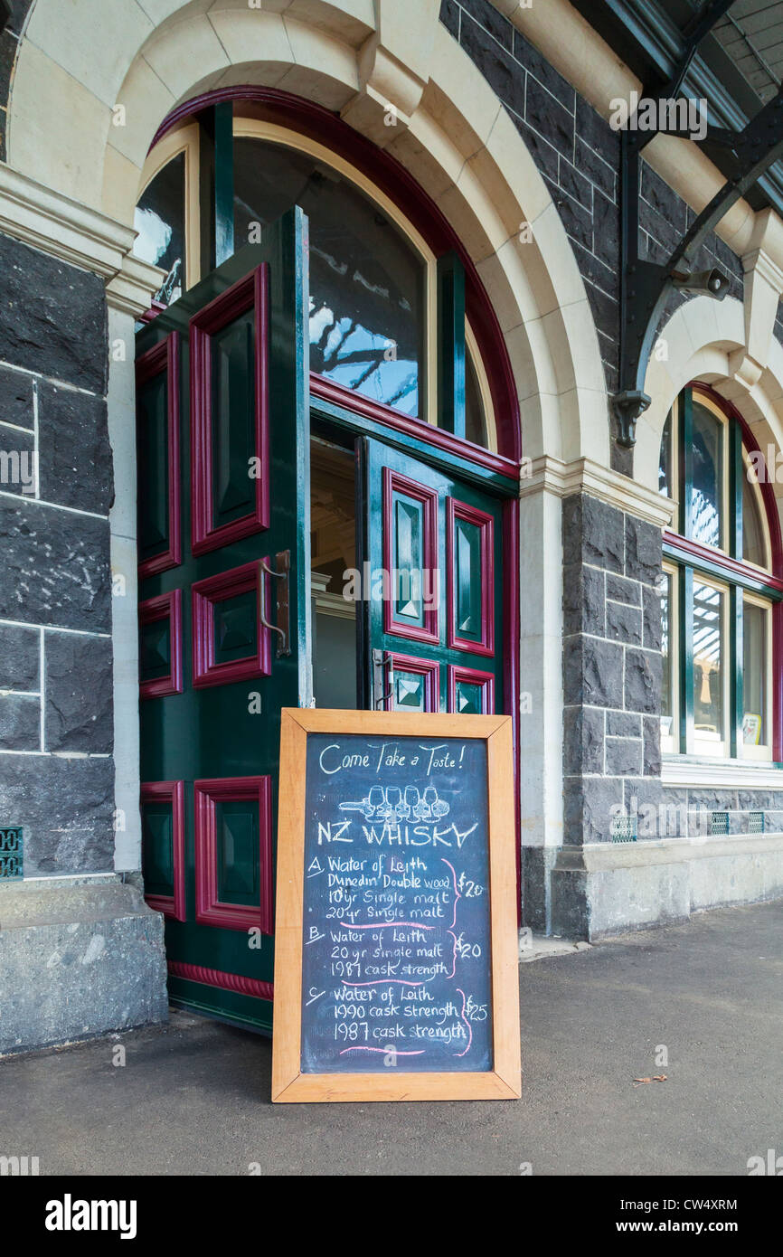 Blackboard offering tasting and sale of New Zealand Whisky, Dunedin Railway Staion, Otago. - Stock Image