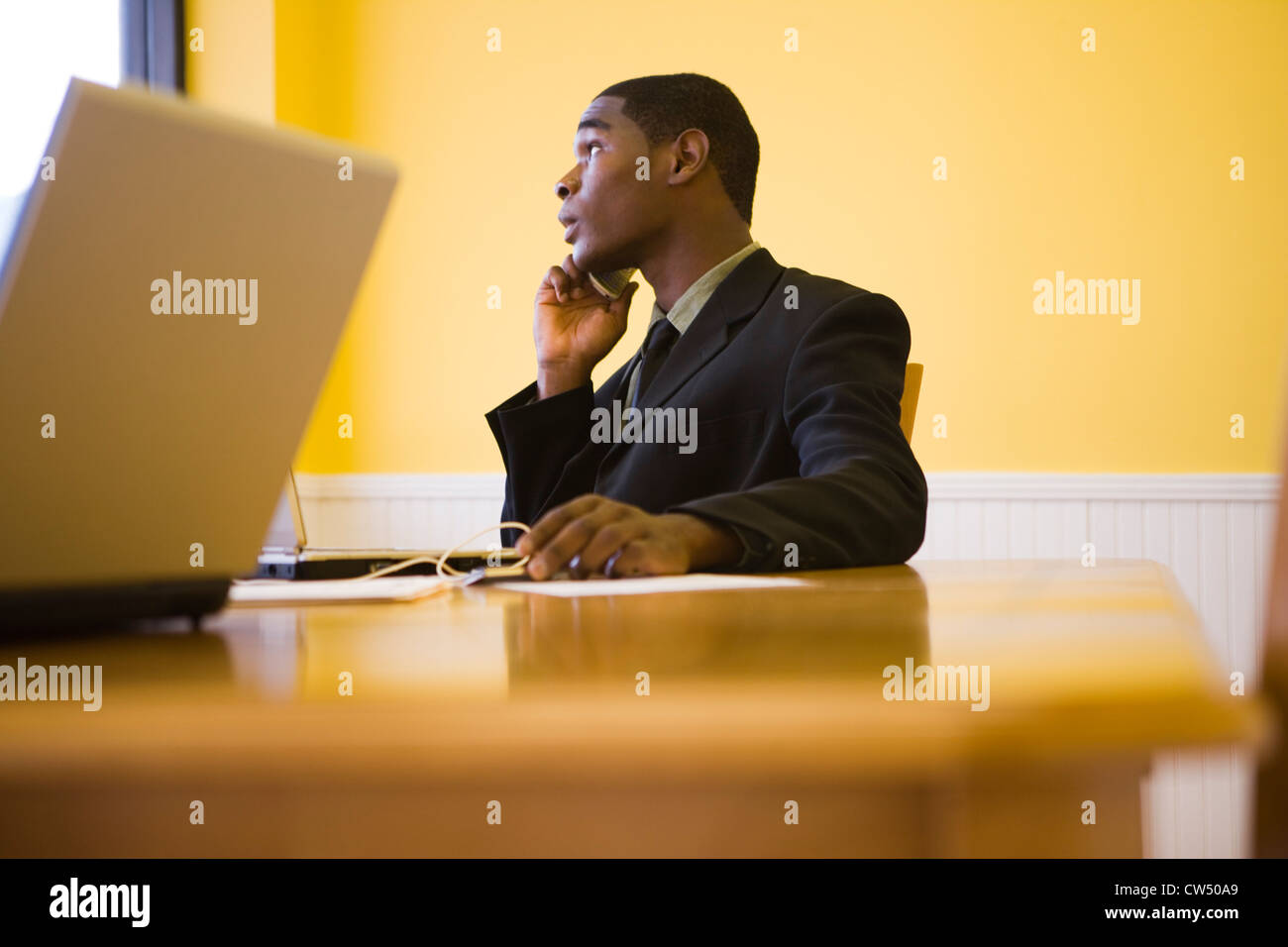 Businessman in full suit using mobile phone and laptop in an office - Stock Image