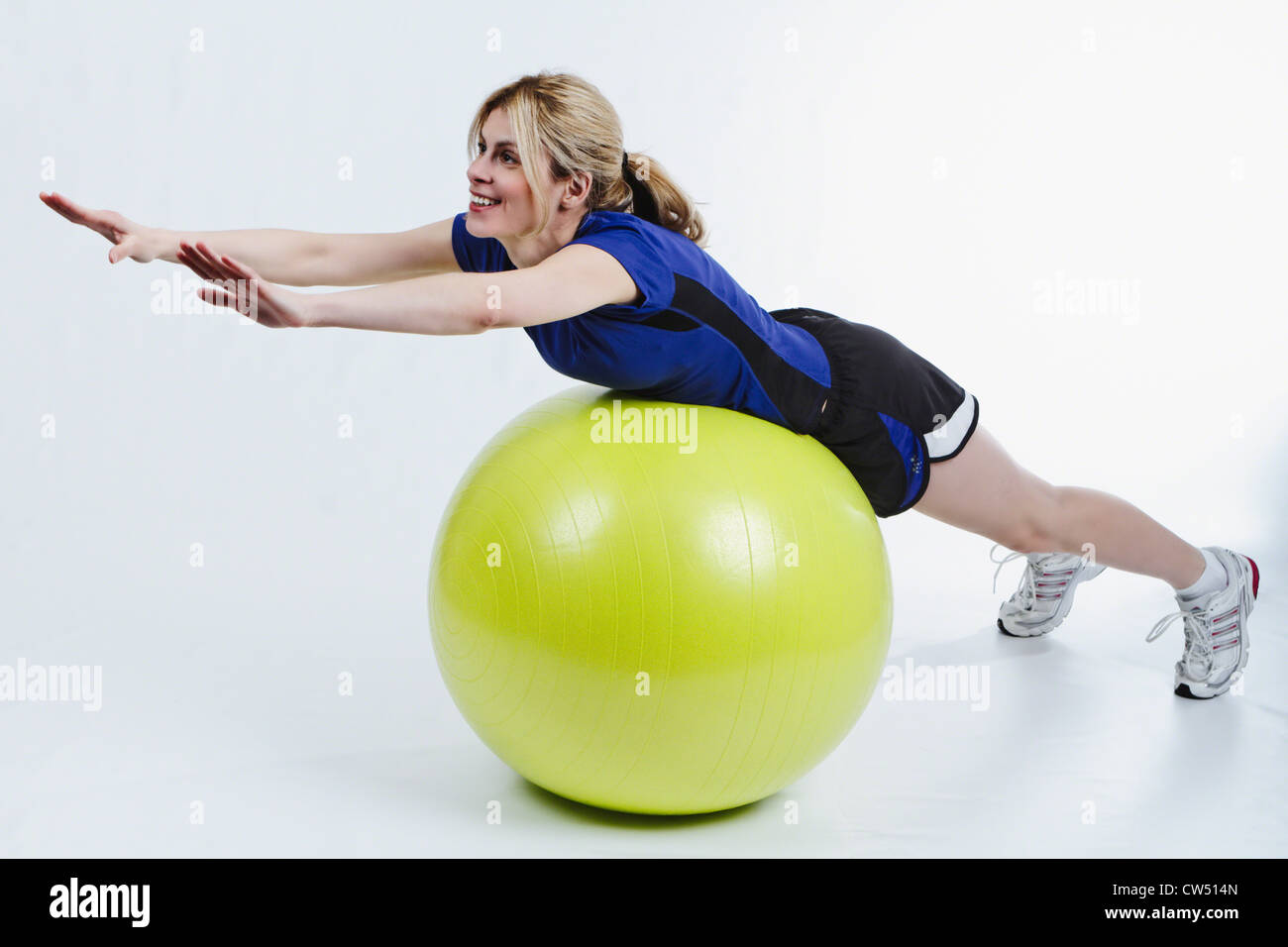 Woman Lying on Belly on Exercise Ball and Stretching - Stock Image