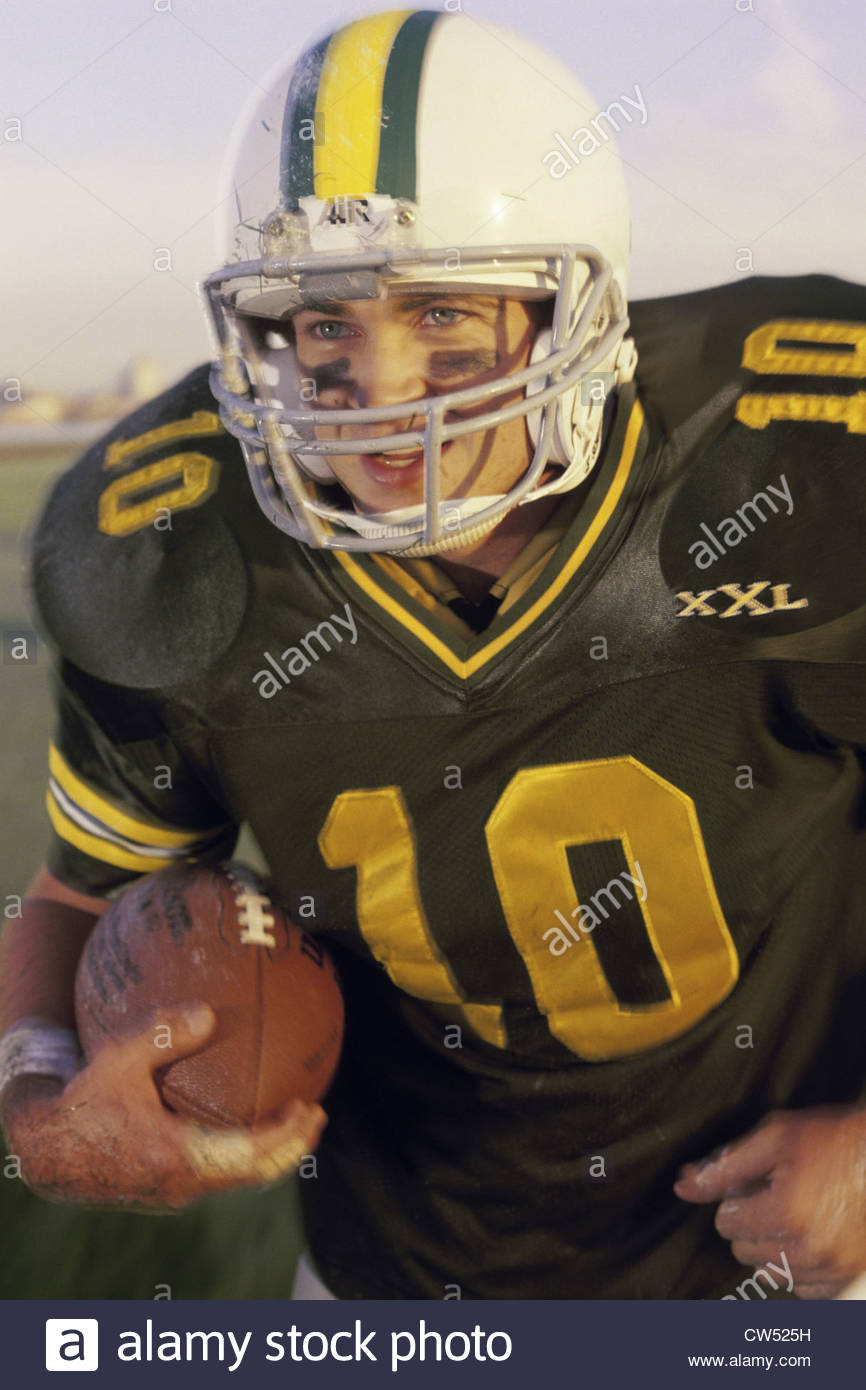 Football player holding a football - Stock Image