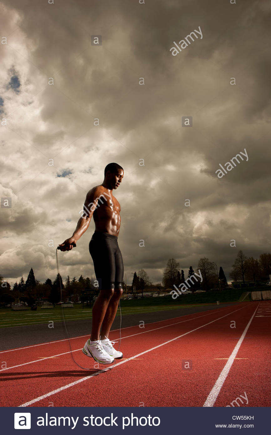 Man jumping rope on track - Stock Image