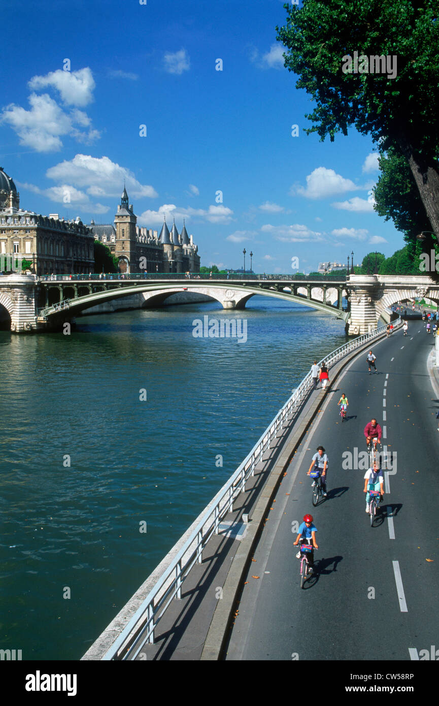 Tourists and Parisians biking along River Seine on open streets in Paris Stock Photo