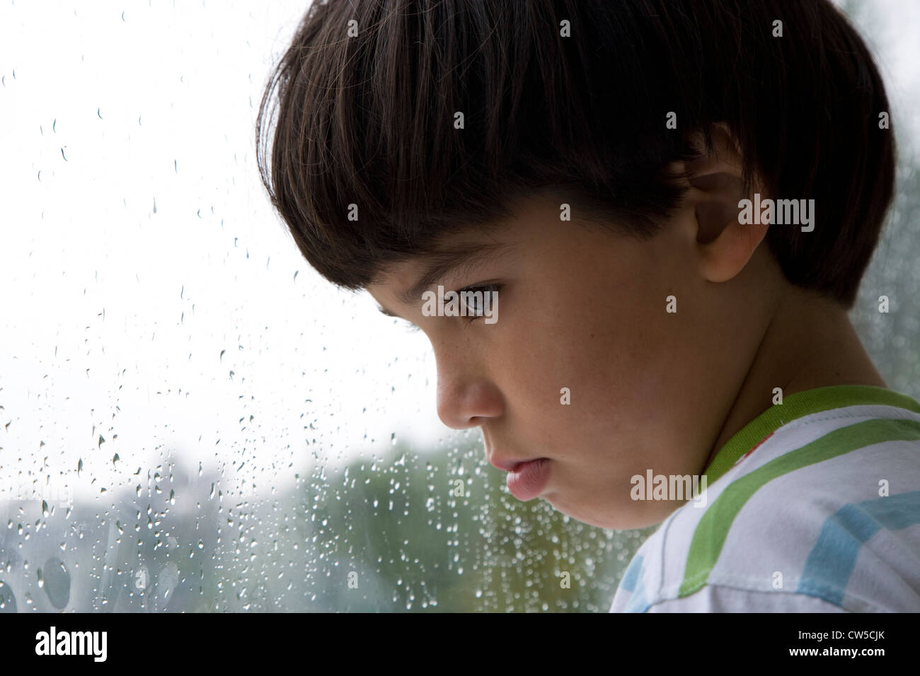 Close-up of a boy looking out a window on a rainy day - Stock Image