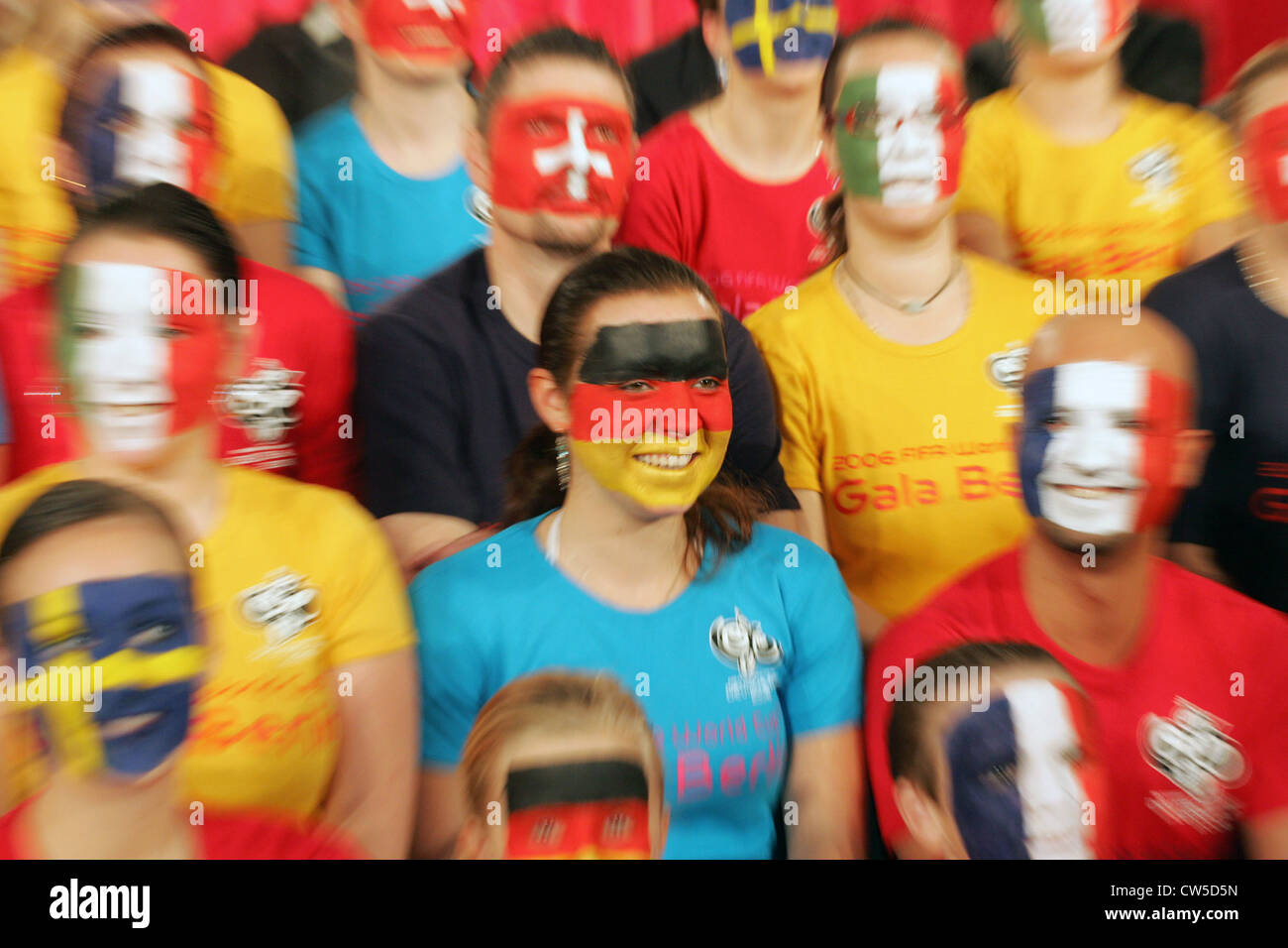 Volunteers of the 2006 World Cup with painted faces - Stock Image