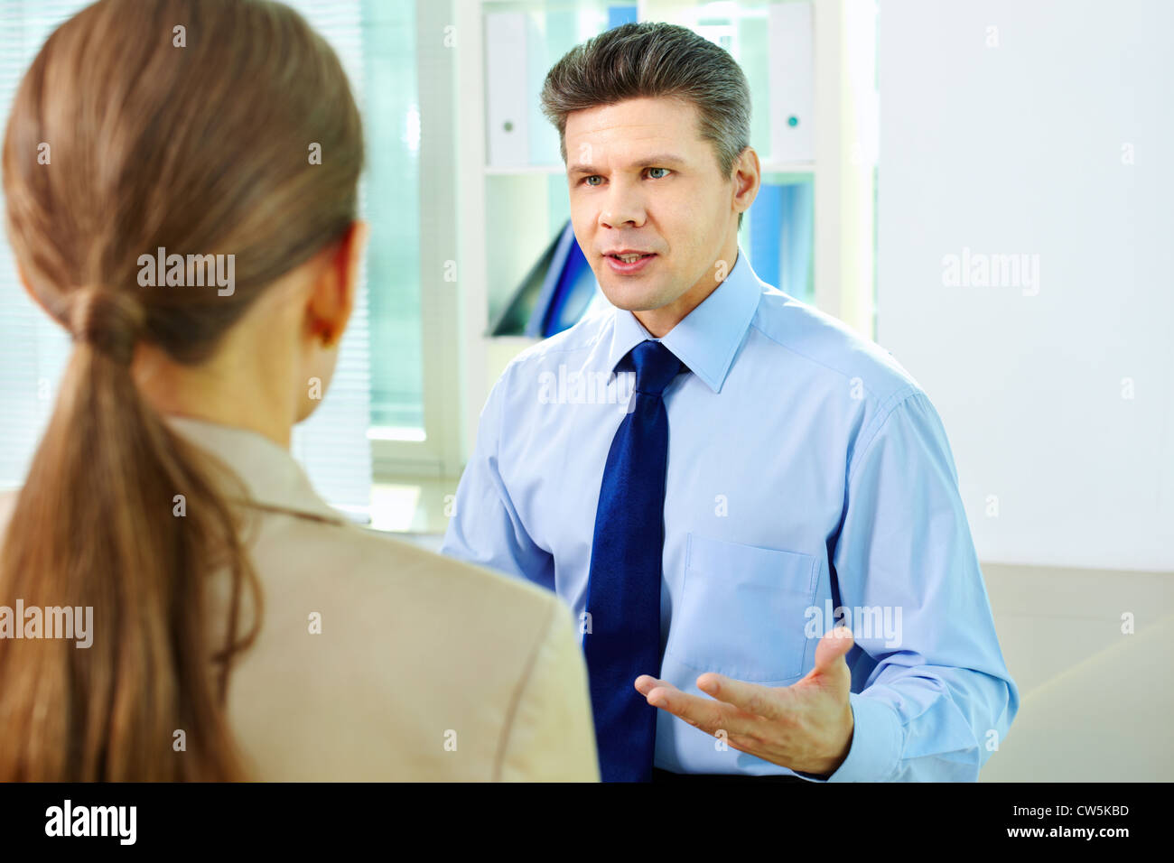Businessman looking at his female colleague during conversation - Stock Image