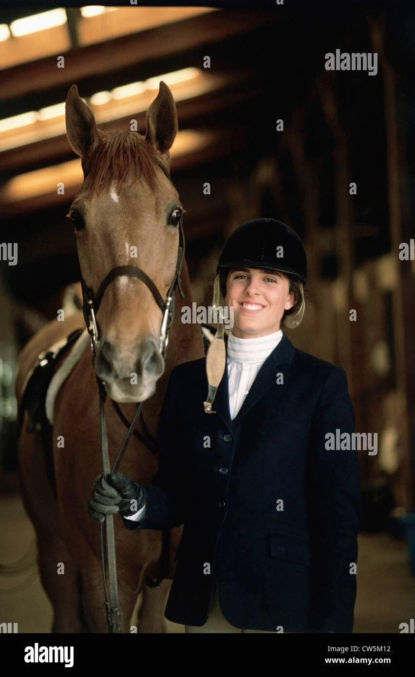 Portrait of a female jockey standing with a horse Stock Photo