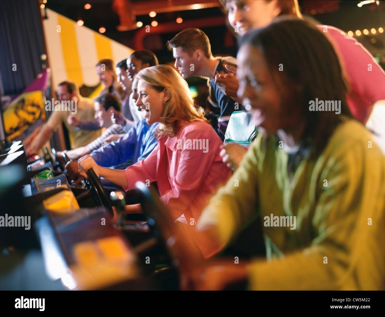 People playing video games in an amusement arcade - Stock Image
