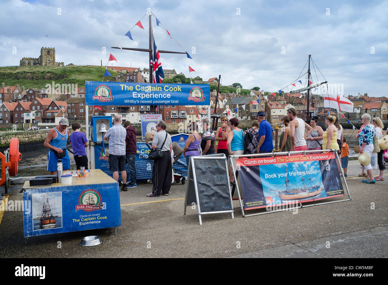 Holidaymakers queuing for a boat trip at Whitby Harbour - Stock Image