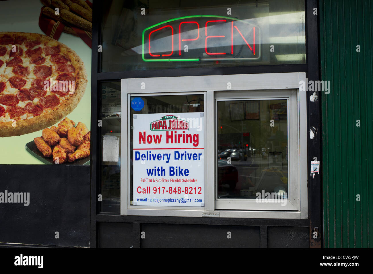 a hiring sign for a delivery driver with bike in a window of a papa johns pizza franchise