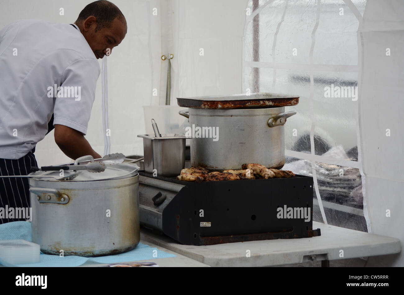 Chef preparing Afro-Caribbean food on a market stall - Stock Image
