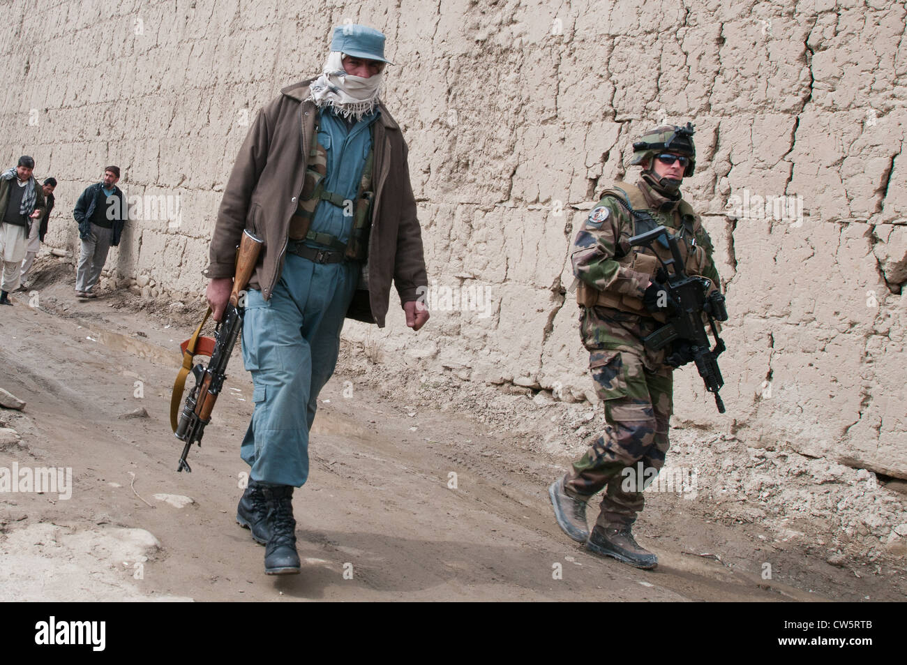 An Afghan policeman and French military policeman from joint forces patrol around compounds during their mission - Stock Image