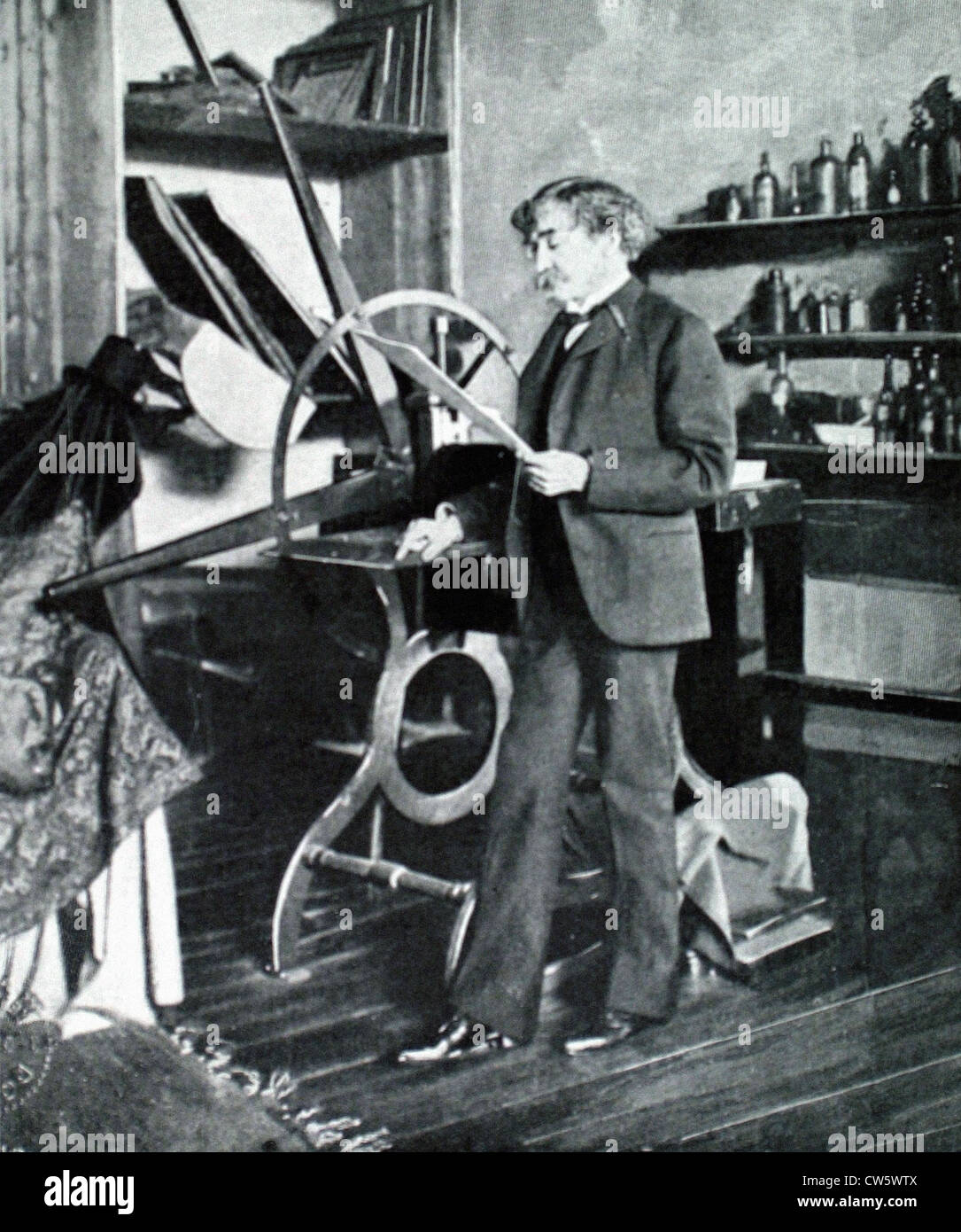 Painter James McNeil Whistler standing by his etching press (1903) - Stock Image