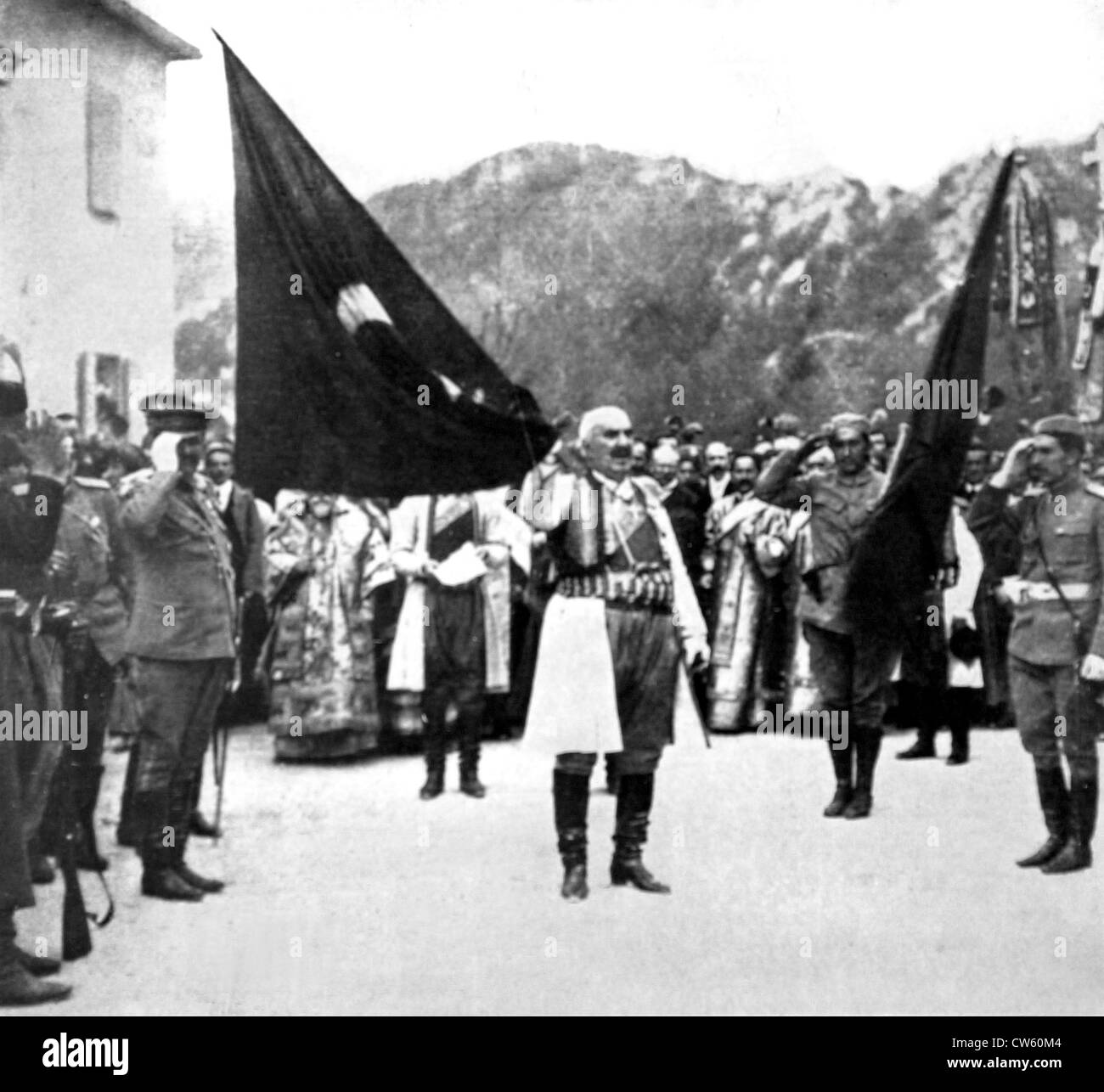 With keys Scutari in one hand King Nicholas Montenegro unfolds flag captured from Turks in front his subjects (1913) - Stock Image