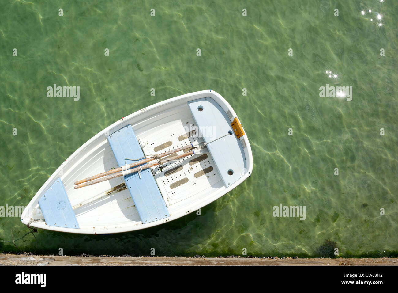 Small rowing boat moored to St. Ives pier in Cornwall UK. - Stock Image