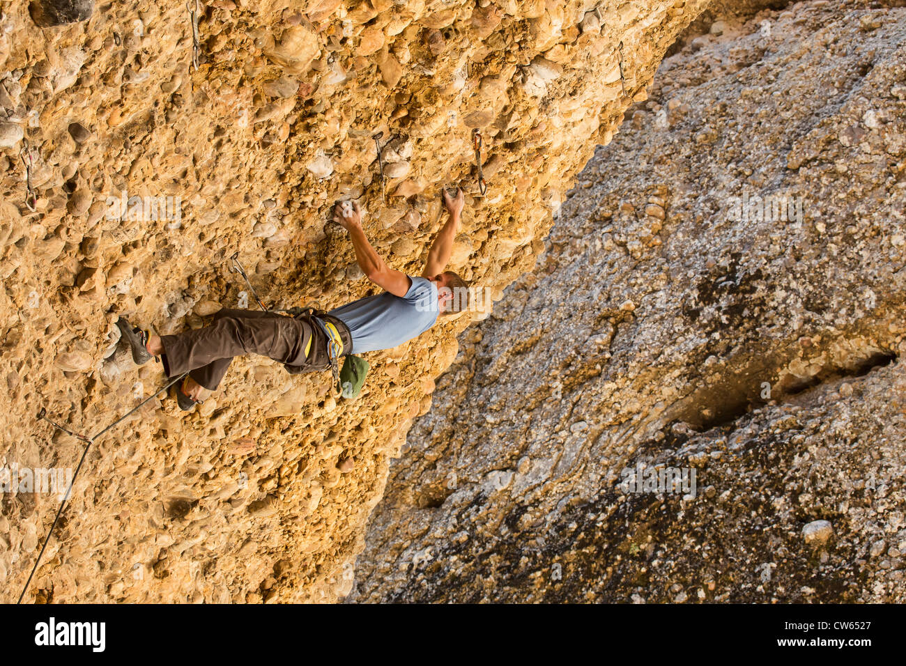 Man high on a rock wall attempting to maneuver around an overhang.  Summer time in the Utah mountains, sunny and Stock Photo