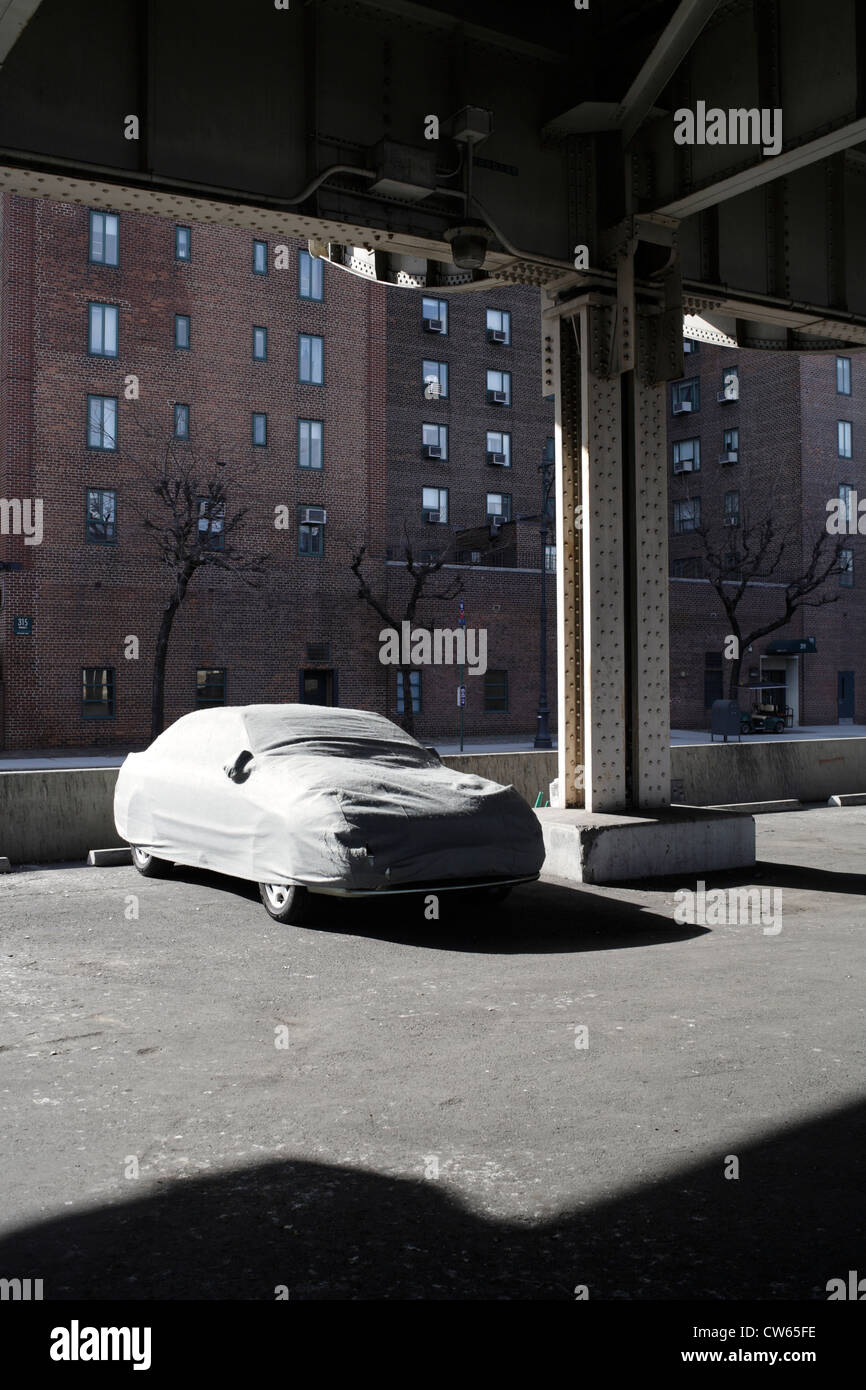 parked car with dust cover in city - Stock Image