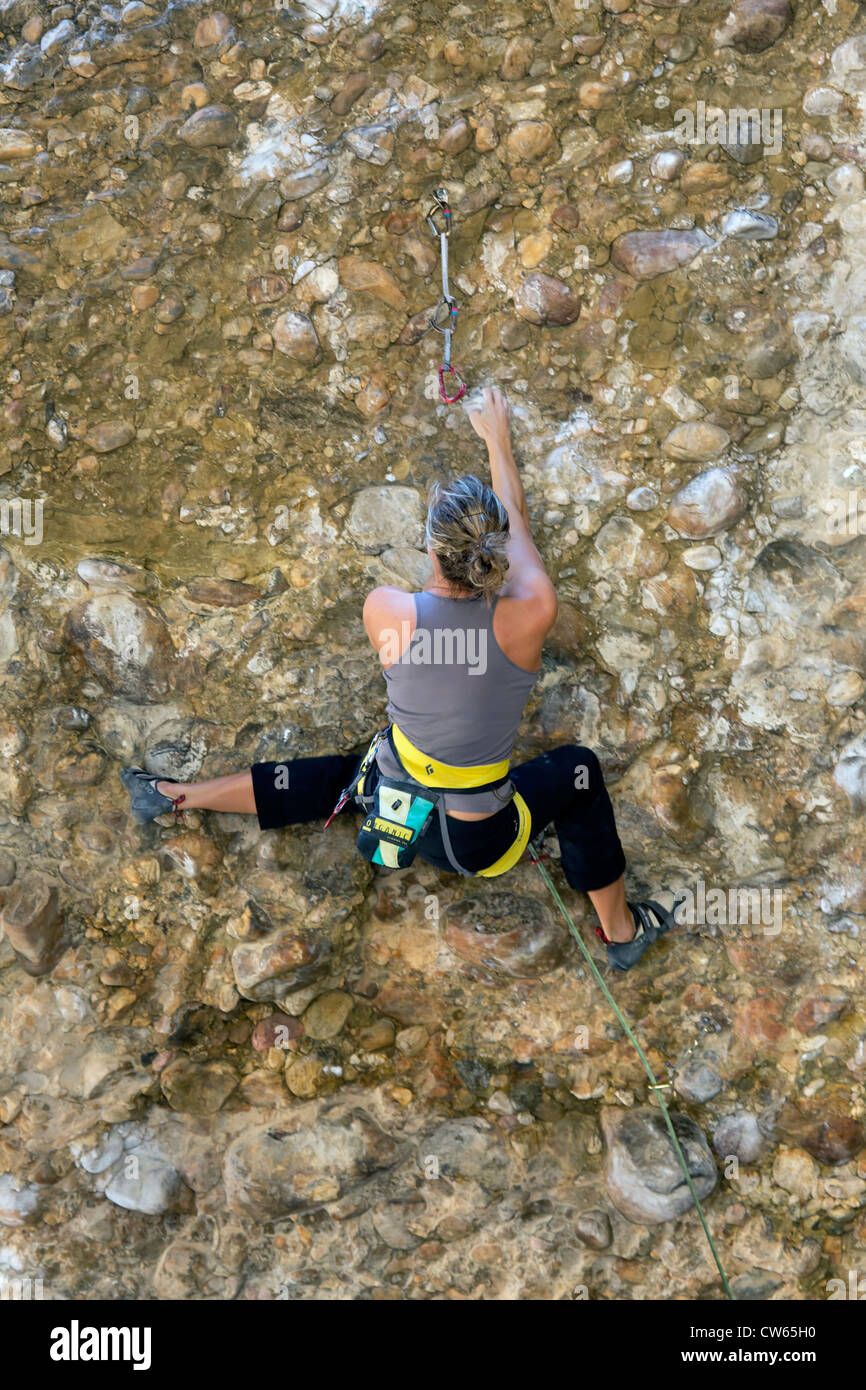 Woman high on a rock wall attempting to maneuver around an overhang.  Summer time in the Utah mountains, sunny and Stock Photo
