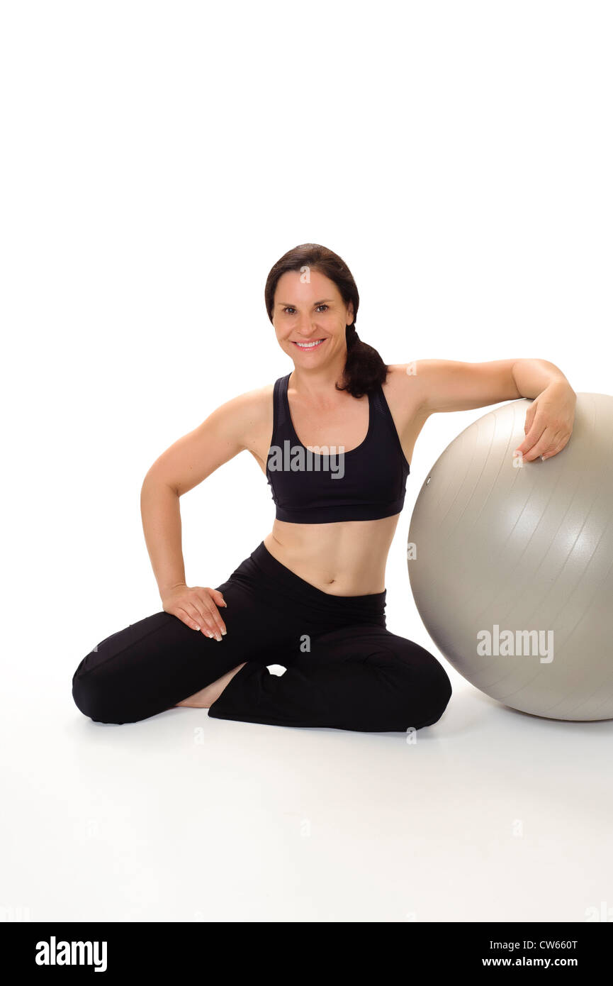 Portrait of a beautiful, physically fit woman in her 40s wearing workout clothing, smiling and leaning on an exercise - Stock Image