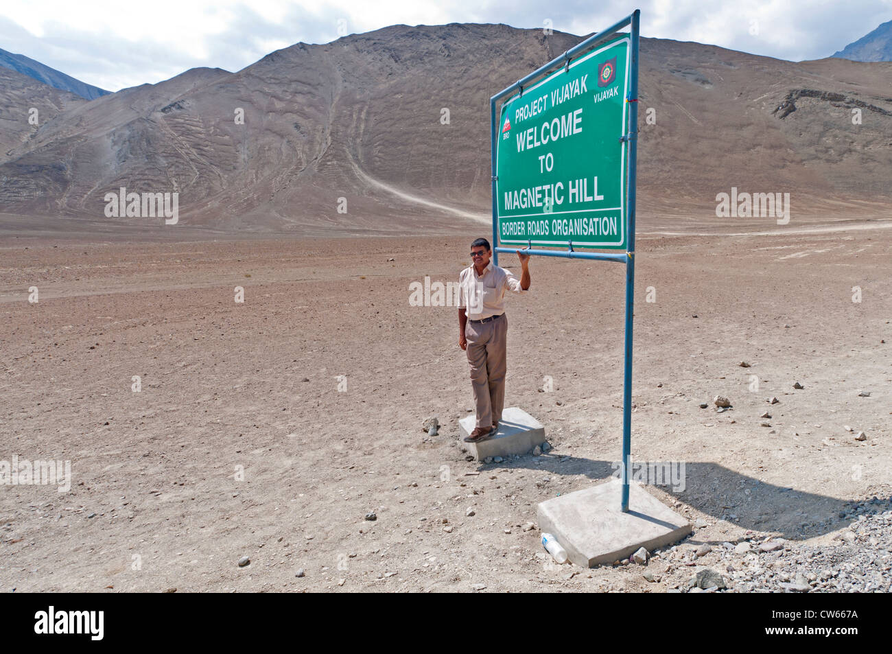 Indian man standing by the Welcome to Magnetic Hill sign on the Leh-Kargil-Srinagar Highway, Ladakh, India - Stock Image
