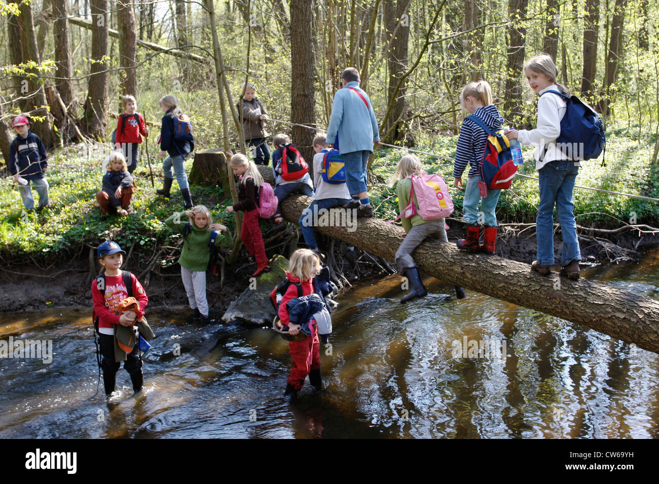 chidren of a grade of school playing at a creek - Stock Image