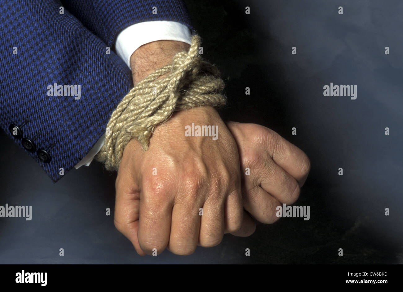 hands of a business man in chains - Stock Image