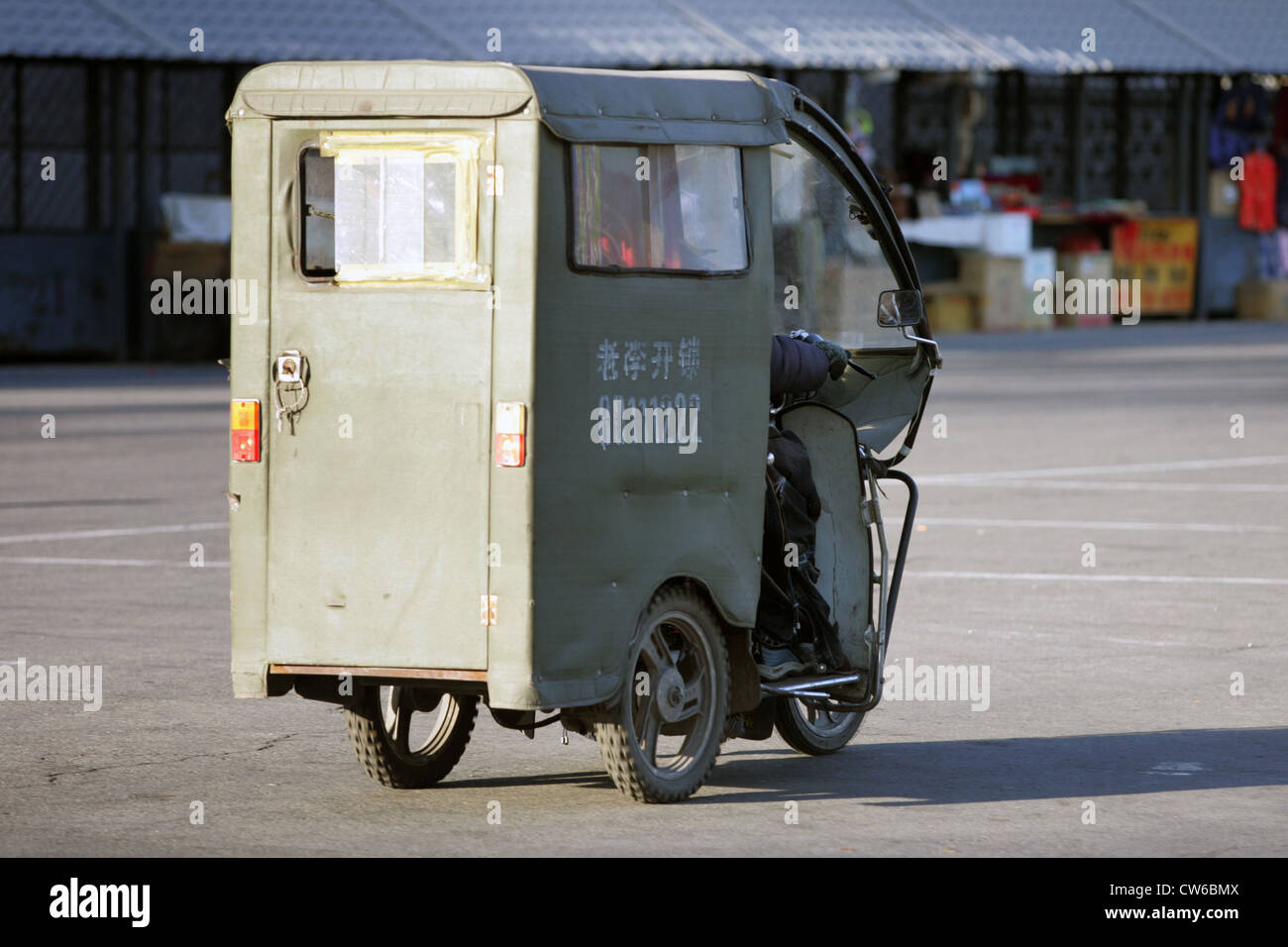 Beijing, a motorized tricycle in traffic - Stock Image