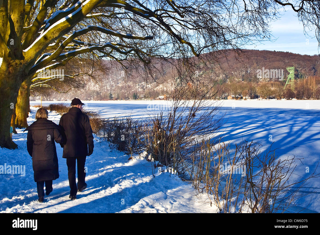 couple at frozen Baldeney Lake, in the background a pit frame of coal mine Carl Funcke, Germany, North Rhine-Westphalia, Stock Photo