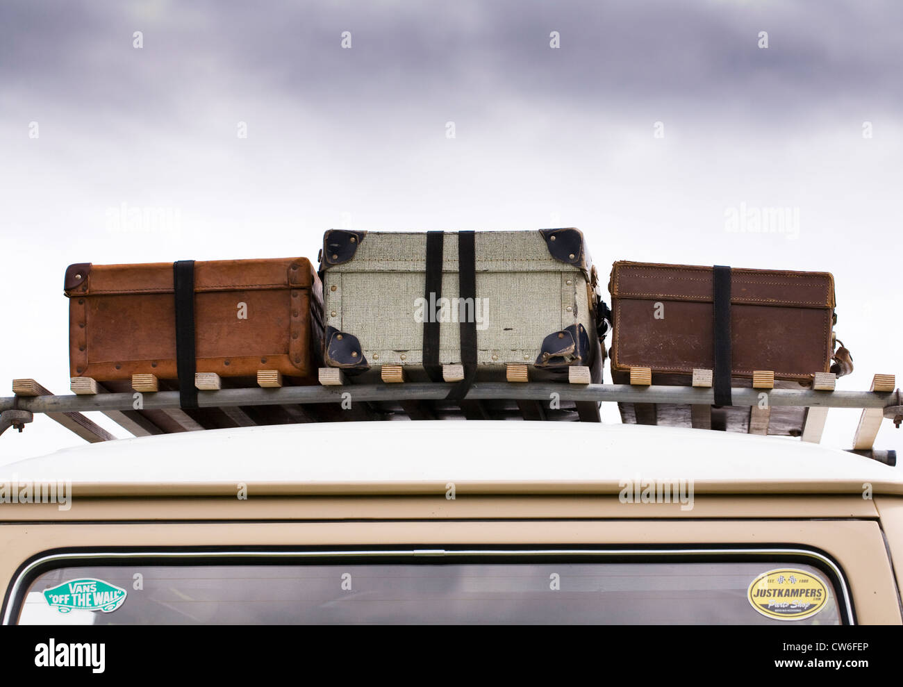 Three old suitcases on an old VW campervan. - Stock Image