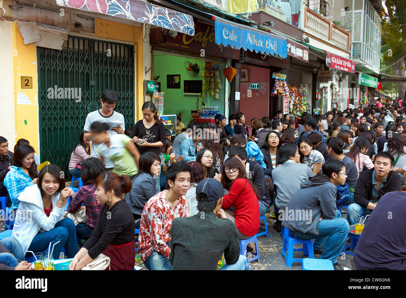A crowd of people sitting in the streets front of an outdoor cafe with the old St. Joseph's Cathedral in the - Stock Image