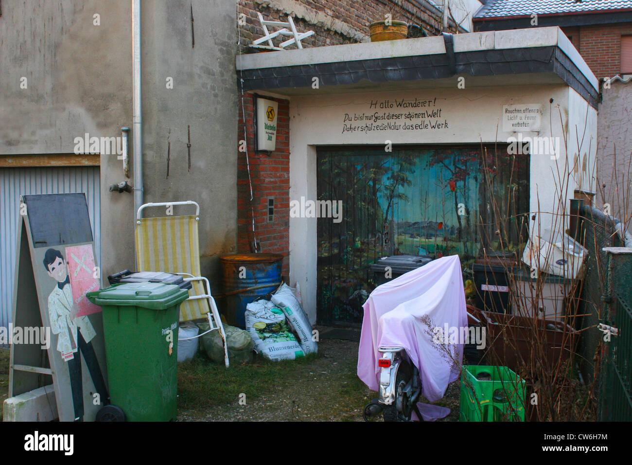 painting on a garage with writing: Hallo Wanderer! Du bist nur Gast dieser schoenen Welt. Daher schuetze die  Natur, - Stock Image