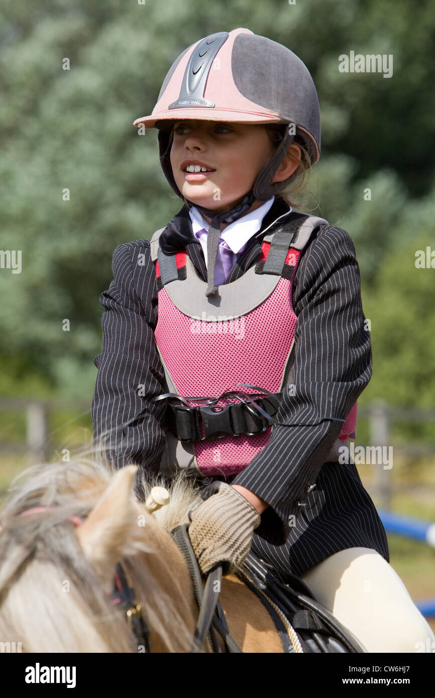 A young girl wearing safety equipment and clothing while sat on her pony - Stock Image