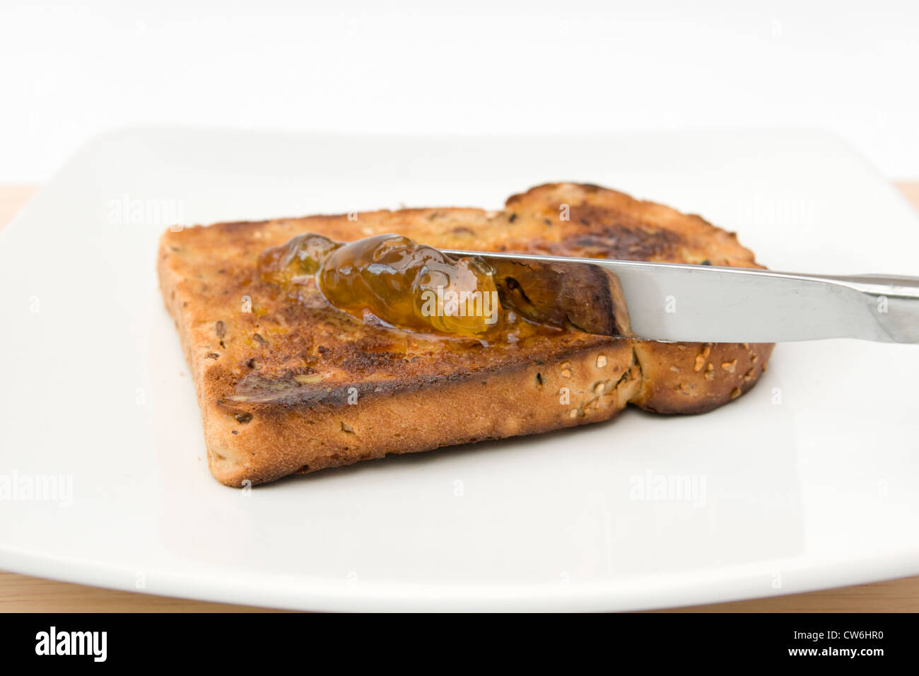 Spreading orange marmalade on slice of granary bread on white plate against white background - Stock Image