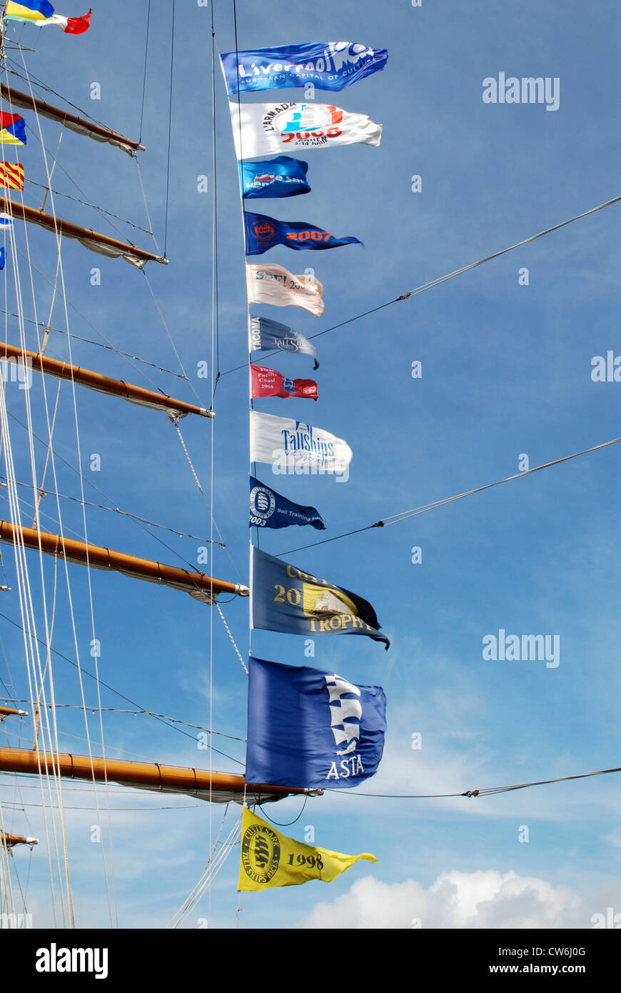 participation flags of tall ship blowing in the wind - Stock Image