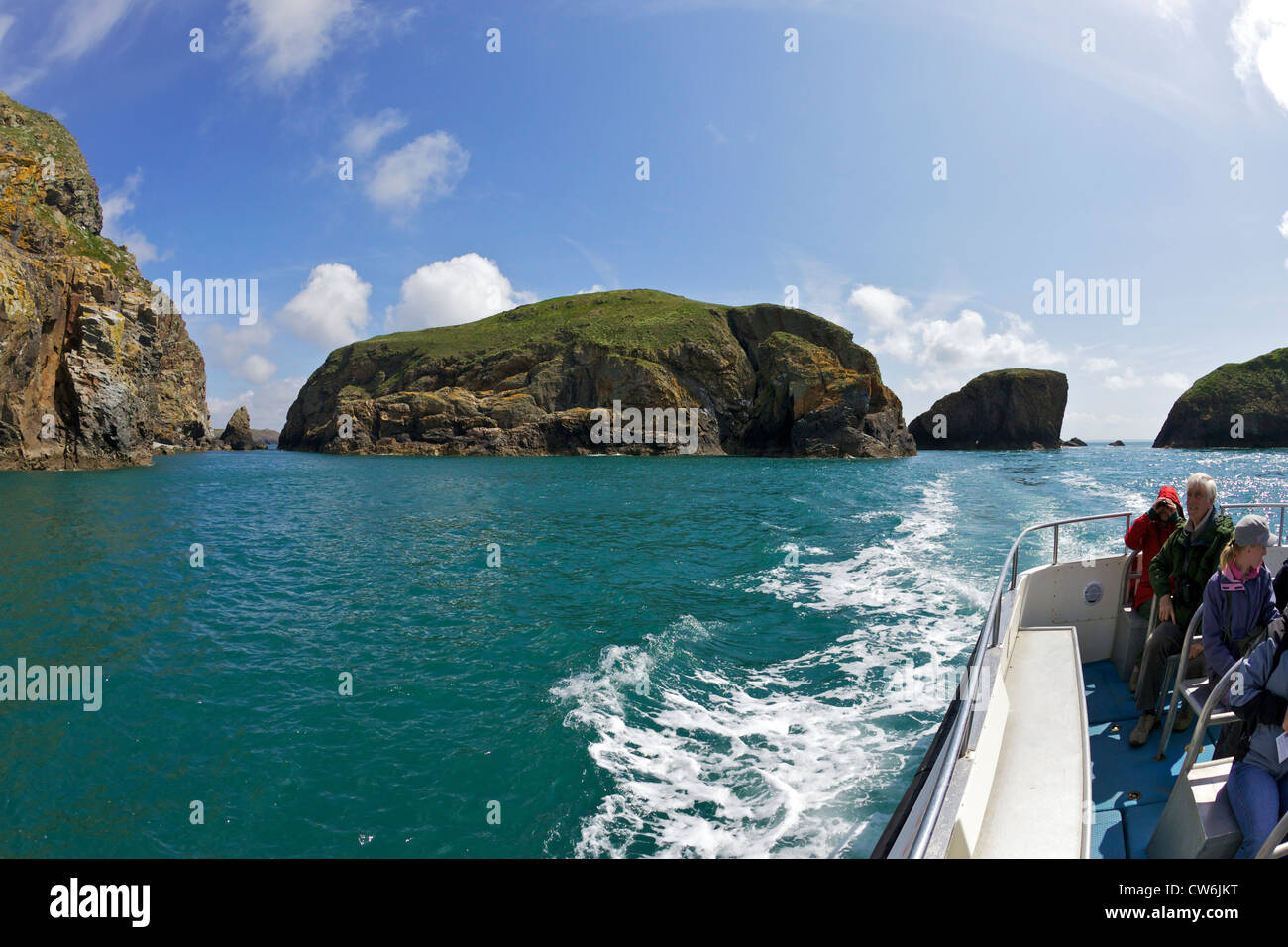 Tourists enjoying boat trip around Ramsey Island in spring sunshine, Pembrokeshire National Park, Wales, Cymru, - Stock Image