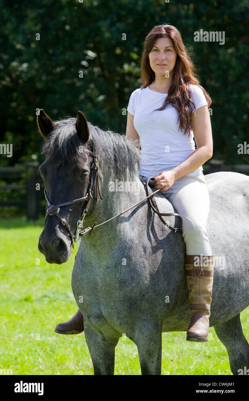 An attractive dark haired young woman riding her horse bareback in a grass field in the English countryside - Stock Image