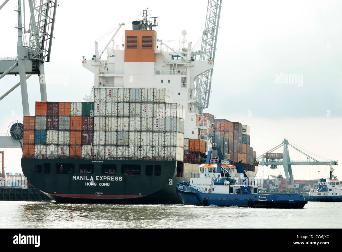 laden containership with tug in Port of Rotterdam Stock Photo