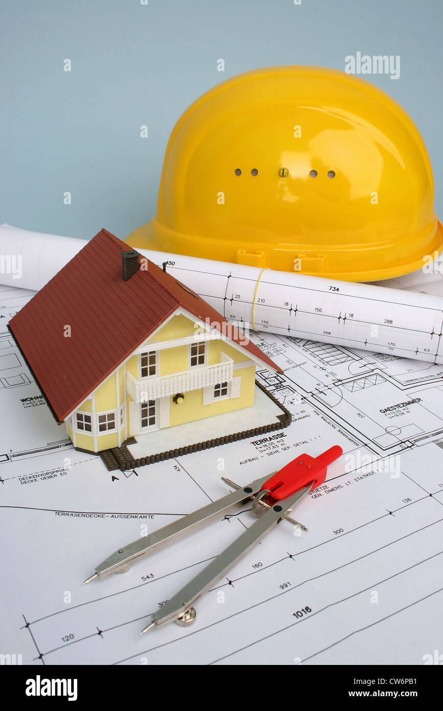 dividers, model of a house and helmet lying on a plan - Stock Image