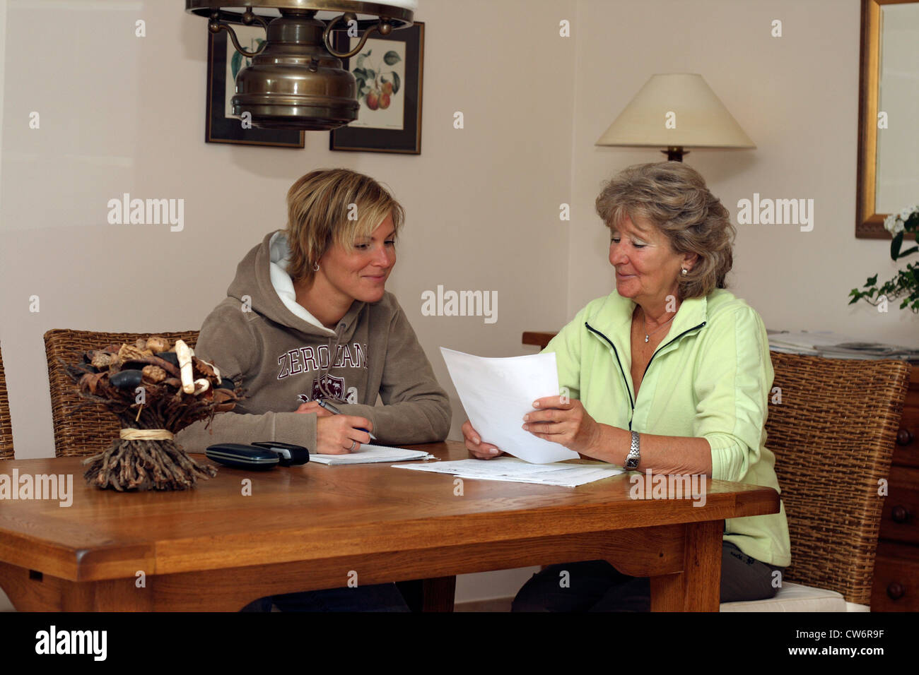 woman is talking with a dog breeder about buying a dog - Stock Image